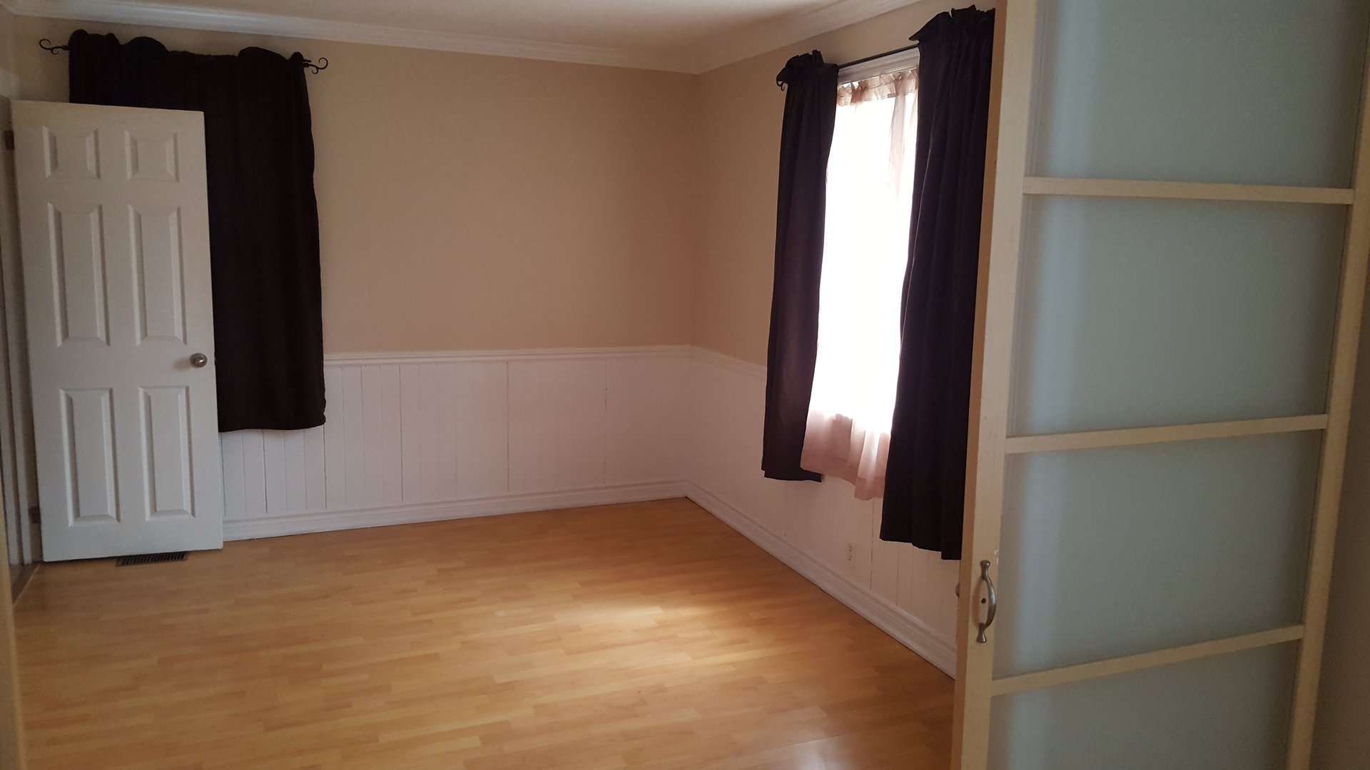 Apartment for rent at 33 Burton St, Belleville, ON. This is the empty room with natural light and hardwood floor.