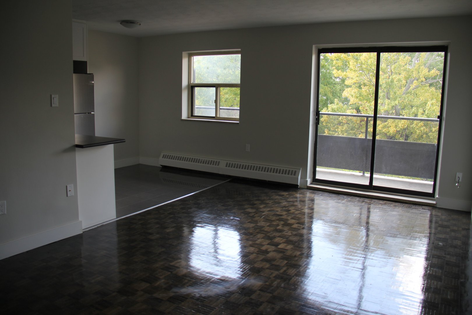 Apartment for rent at 141 Main St S, Brampton, ON. This is the empty room with natural light and hardwood floor.