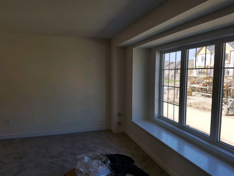 House for rent at 77 Baycliffe Cres, Brampton, ON. This is the empty room with natural light and carpet.