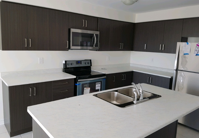 House for rent at 77 Baycliffe Cres, Brampton, ON. This is the kitchen with stainless steel and kitchen island.