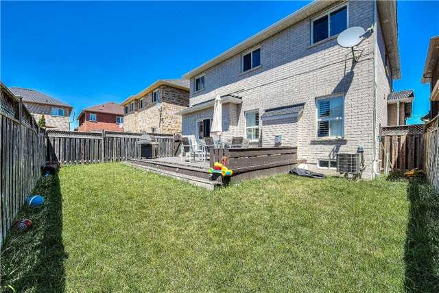 House for rent at 118 Earlsbridge Blvd, Brampton, ON. This is the backyard with deck, lawn and central ac.