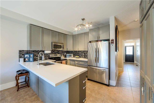 House for rent at 118 Earlsbridge Blvd, Brampton, ON. This is the kitchen with kitchen bar, stainless steel and tile floor.