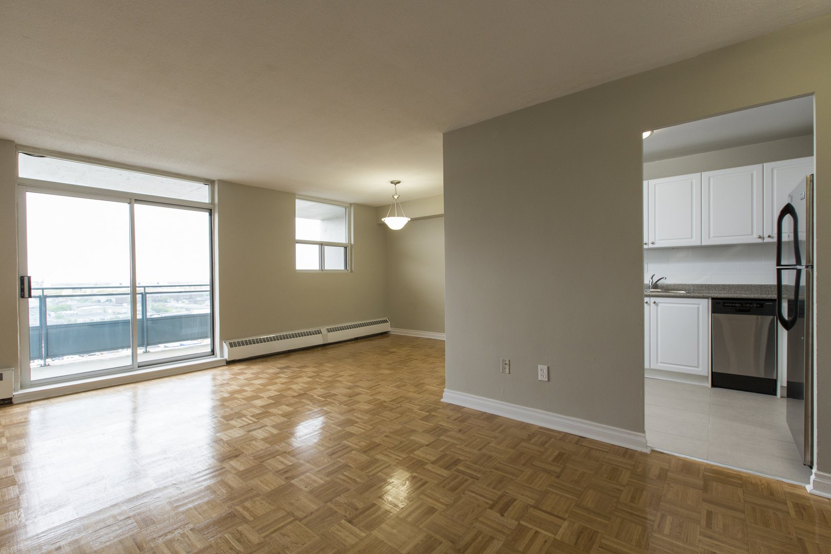 Apartment for rent at 33 Kennedy Rd S, Brampton, ON. This is the empty room with natural light, tile floor and hardwood floor.