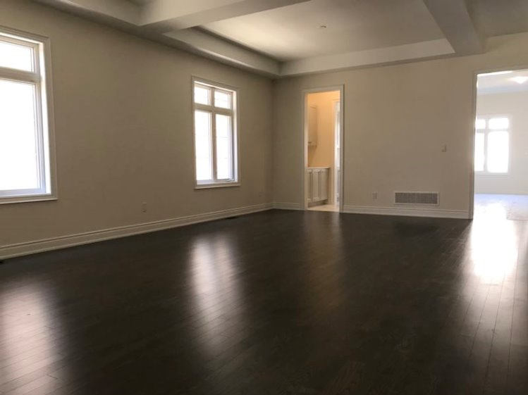 House for rent at 333 Rivermont Road, Brampton, ON. This is the empty room with natural light, beamed ceiling and hardwood floor.