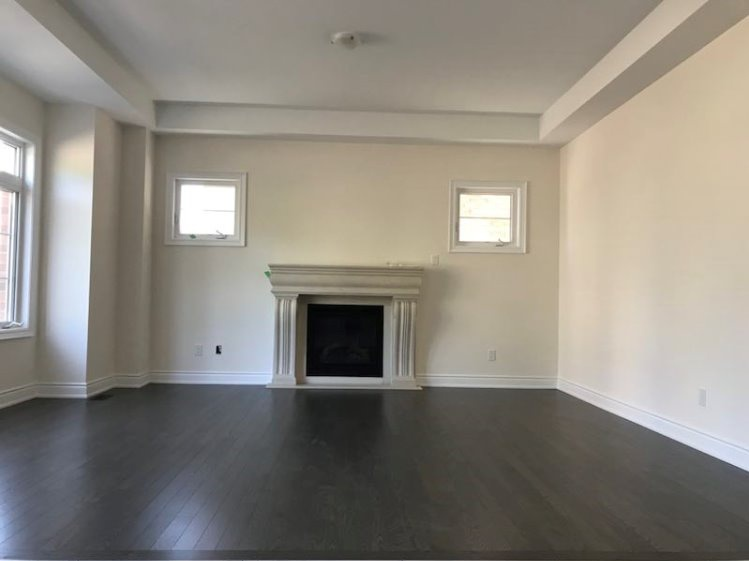 House for rent at 333 Rivermont Road, Brampton, ON. This is the empty room with natural light, fireplace and hardwood floor.