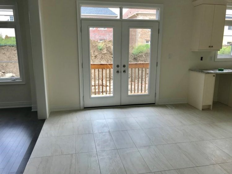 House for rent at 333 Rivermont Road, Brampton, ON. This is the empty room with natural light, french doors, hardwood floor and tile floor.