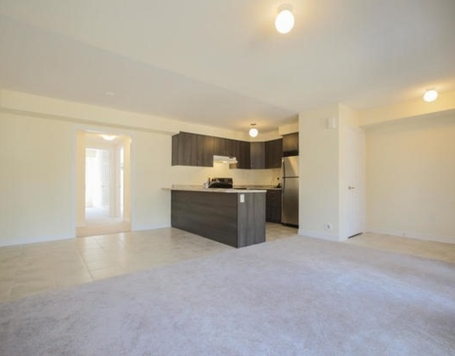 House for rent at 200 Veterans Drive, Brampton, ON. This is the empty room with carpet and stainless steel.