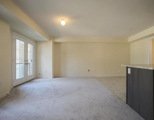 House for rent at 200 Veterans Drive, Brampton, ON. This is the empty room with carpet, french doors, natural light and tile floor.