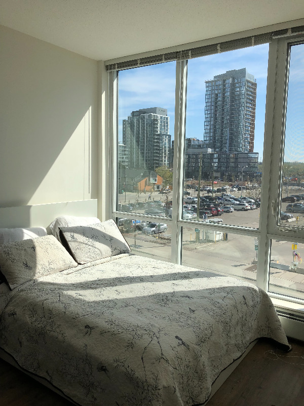 Condo for rent at 450 8 Ave SE, Calgary, AB. This is the bedroom with natural light and hardwood floor.