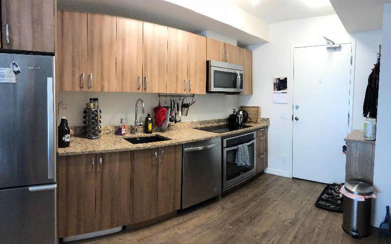 Condo for rent at 450 8 Ave SE, Calgary, AB. This is the kitchen with stainless steel, hardwood floor, microwave, refrigerator, oven and dishwasher.