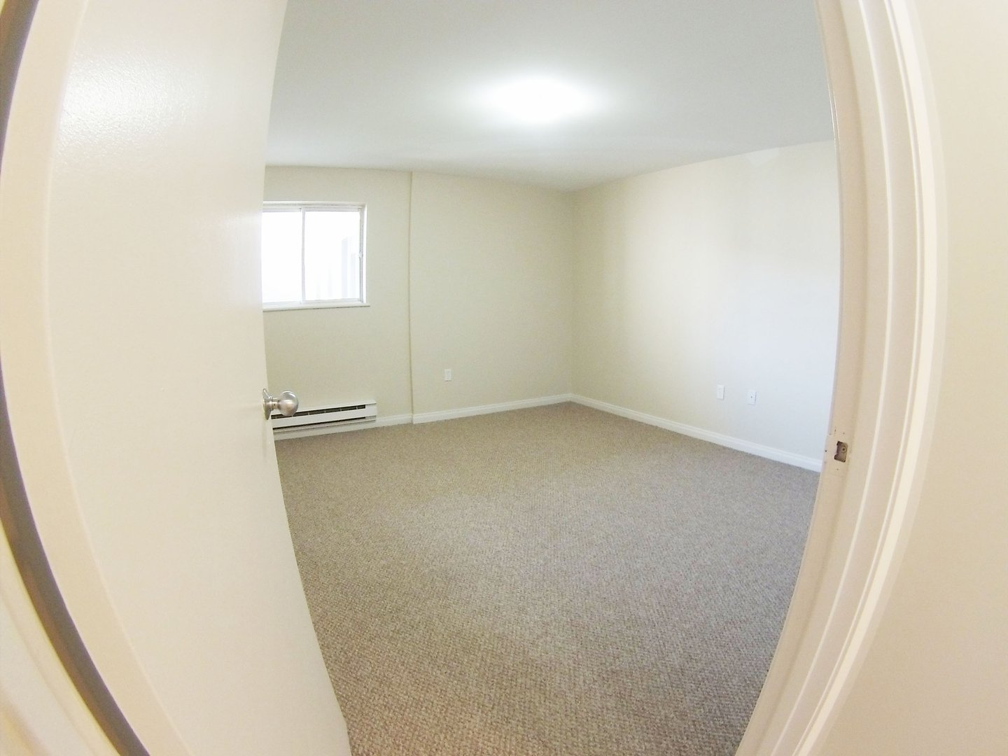 Apartment for rent at 96 Highfield Park Drive B, Dartmouth, NS. This is the empty room with natural light and carpet.