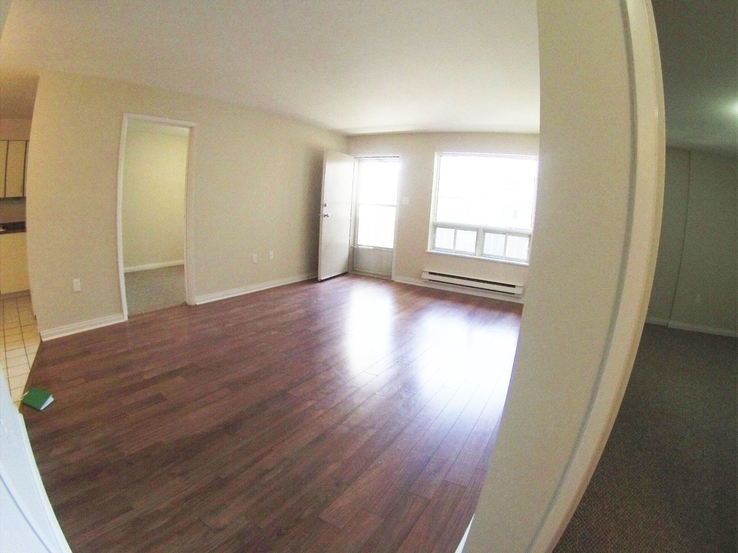 Apartment for rent at 96 Highfield Park Drive B, Dartmouth, NS. This is the empty room with hardwood floor, carpet and natural light.