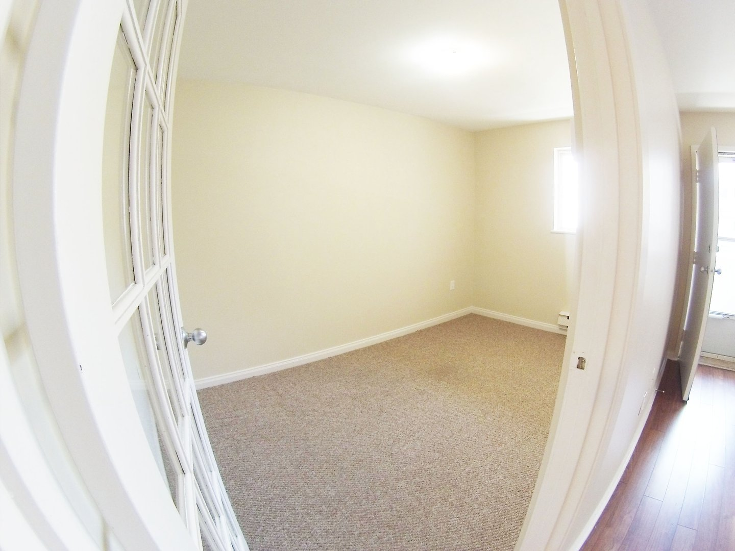 Apartment for rent at 96 Highfield Park Drive B, Dartmouth, NS. This is the empty room with hardwood floor, natural light and carpet.
