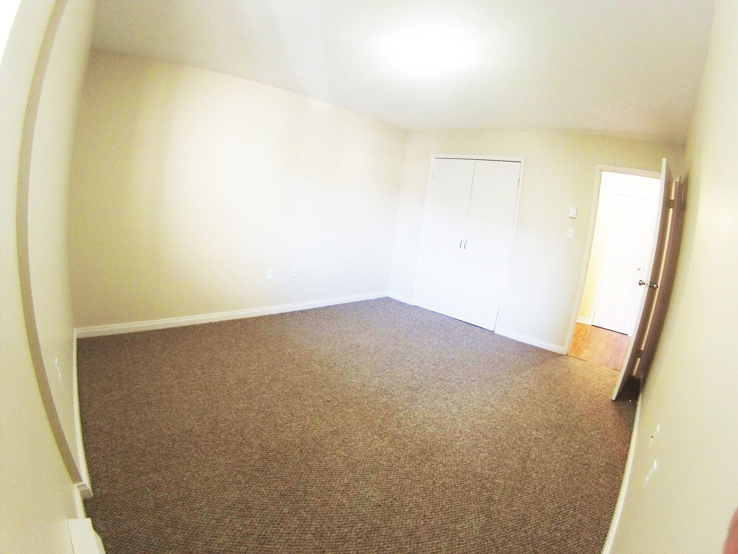 Apartment for rent at 96 Highfield Park Drive B, Dartmouth, NS. This is the empty room with vaulted ceiling, natural light and carpet.