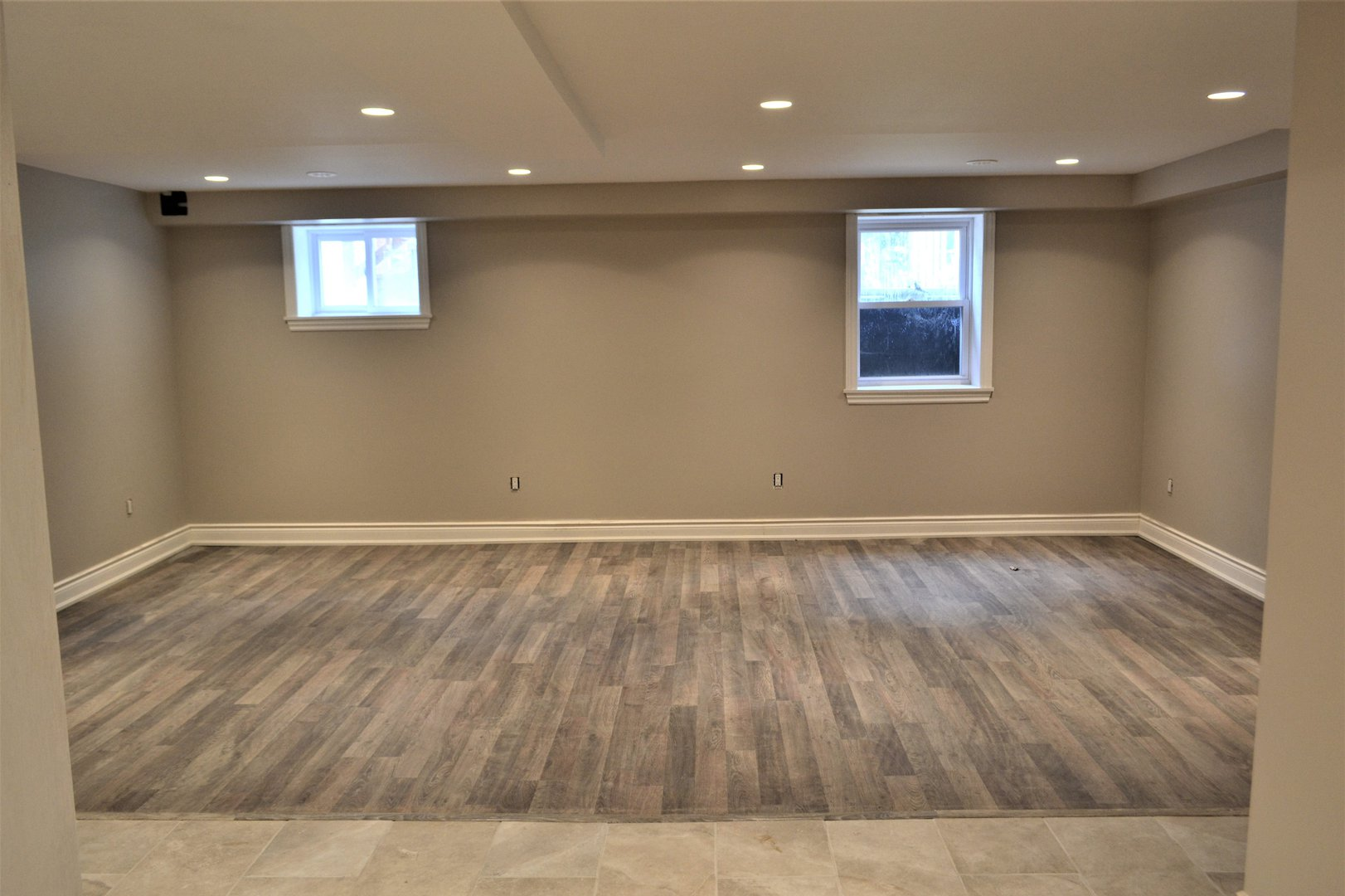 House for rent at 20 Sixth St, Etobicoke, ON. This is the empty room with hardwood floor, natural light and tile floor.