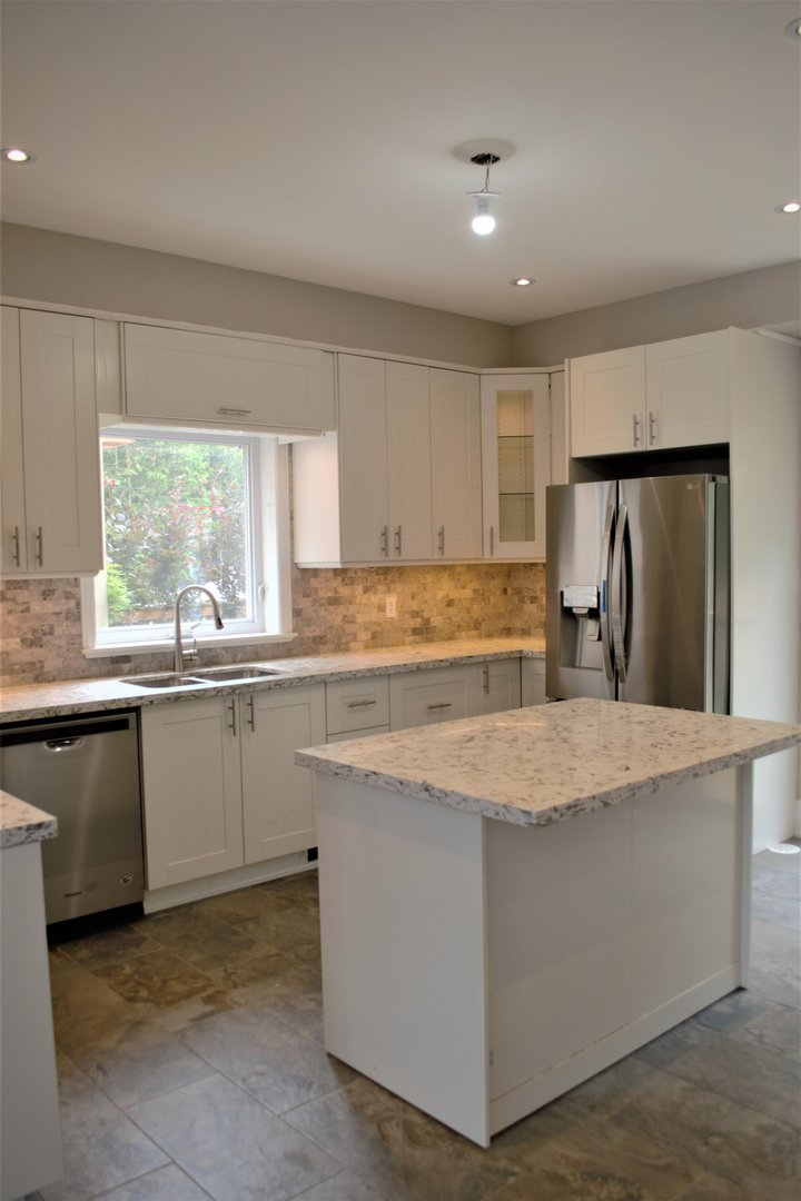 House for rent at 20 Sixth St, Etobicoke, ON. This is the kitchen with natural light, stainless steel, kitchen island and tile floor.