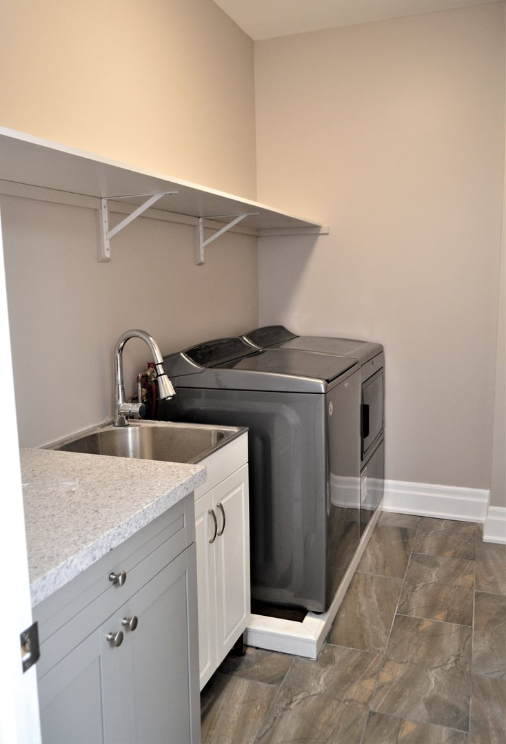 House for rent at 20 Sixth St, Etobicoke, ON. This is the laundry room with hardwood floor.