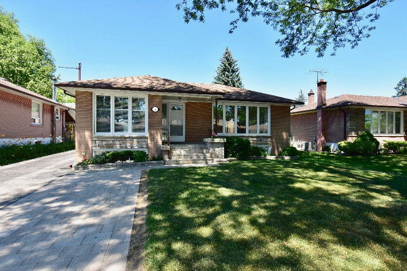 House for rent at 18 Pagebrook Dr, Etobicoke, ON in ranch style. This is the front of the house with lawn and pergola.