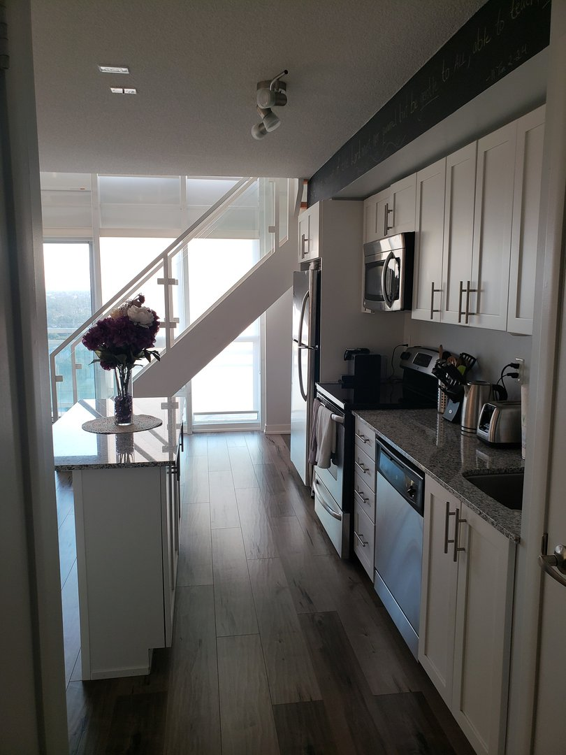 Condo for rent at 155 Legion Rd N, Etobicoke, ON. This is the kitchen with hardwood floor, stainless steel and natural light.