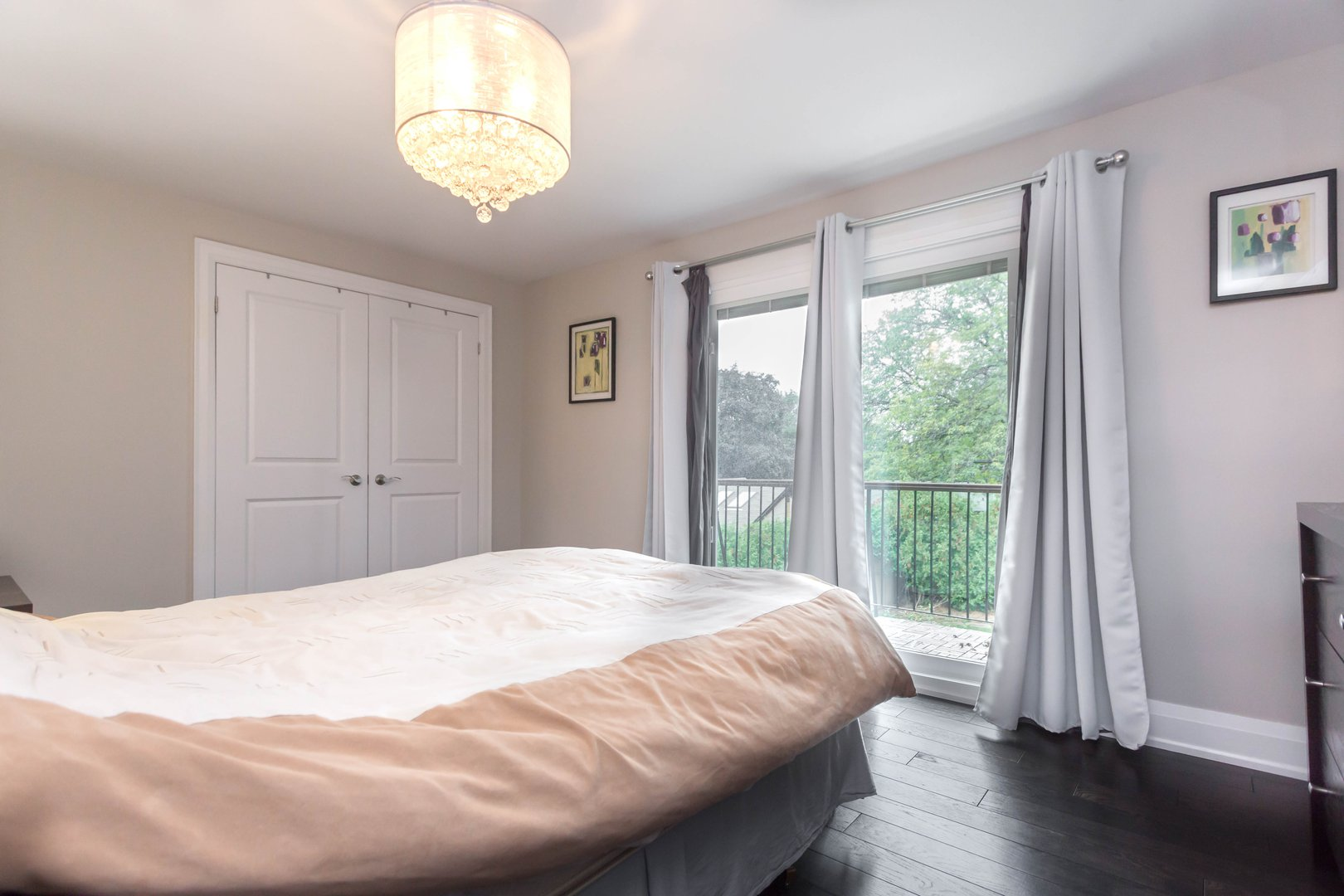 House for rent at 84 Laurel Avenue, Etobicoke, ON. This is the bedroom with notable chandelier, natural light and hardwood floor.