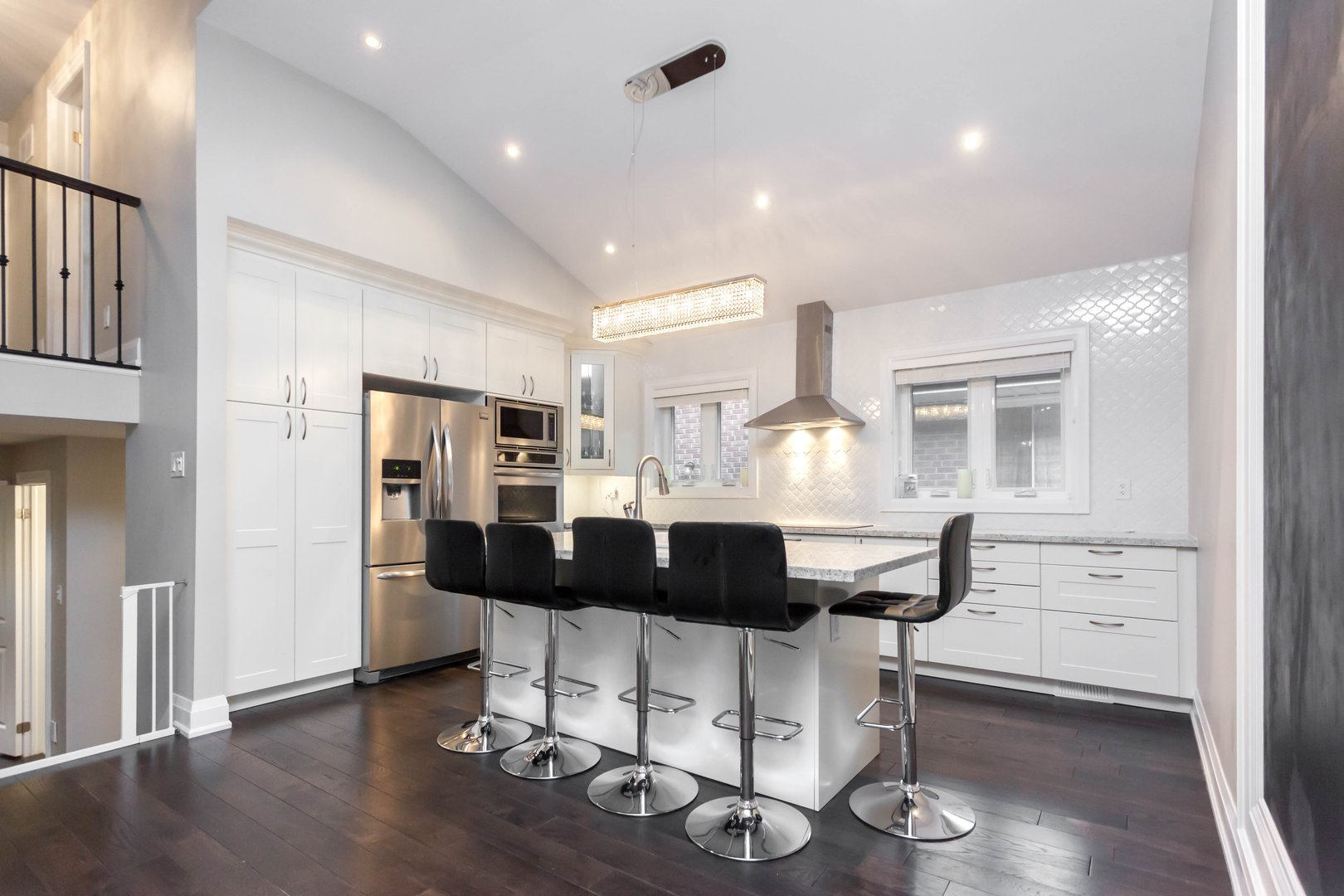House for rent at 84 Laurel Avenue, Etobicoke, ON. This is the kitchen with natural light, kitchen bar, stainless steel, hardwood floor and vaulted ceiling.
