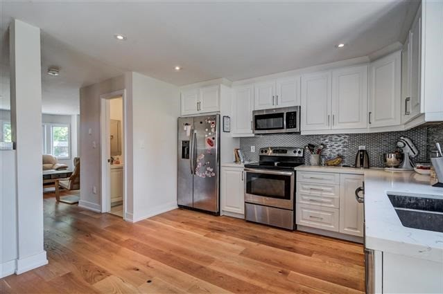 House for rent at 64 Superior Ave, Etobicoke, ON. This is the kitchen with hardwood floor, stainless steel and natural light.