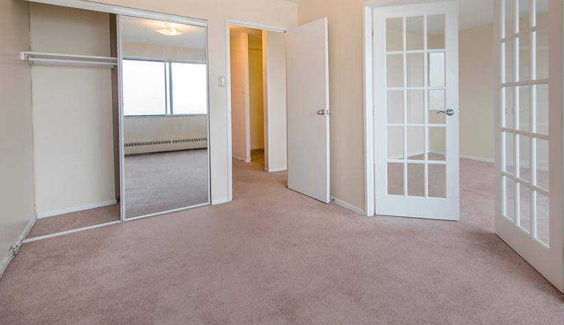 Apartment for rent at 5651 Ogilvie Street, Halifax, NS. This is the empty room with carpet, french doors and natural light.