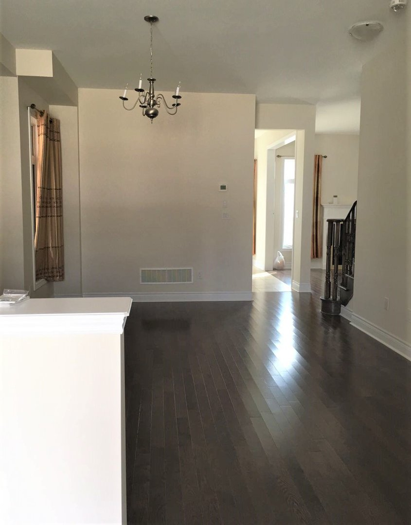 House for rent at 92 Morningside Dr, Halton Hills, ON. This is the empty room with hardwood floor and notable chandelier.