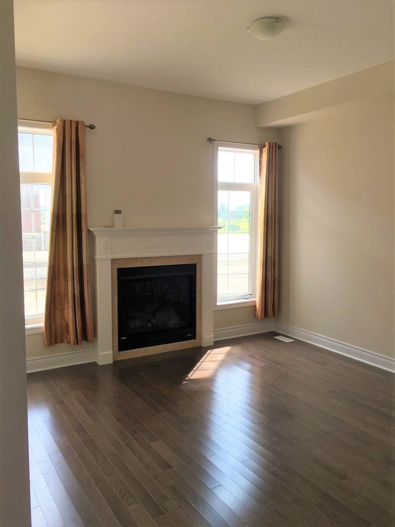 House for rent at 92 Morningside Dr, Halton Hills, ON. This is the empty room with hardwood floor, fireplace and natural light.