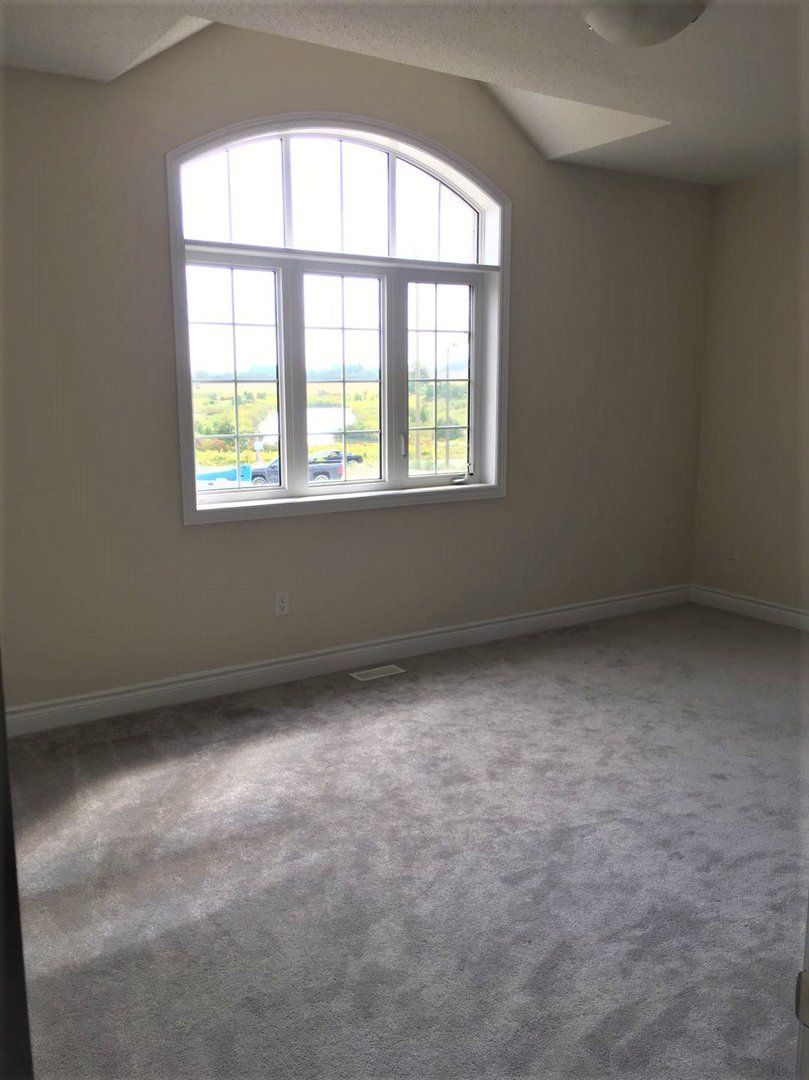 House for rent at 92 Morningside Dr, Halton Hills, ON. This is the empty room with vaulted ceiling, natural light and carpet.