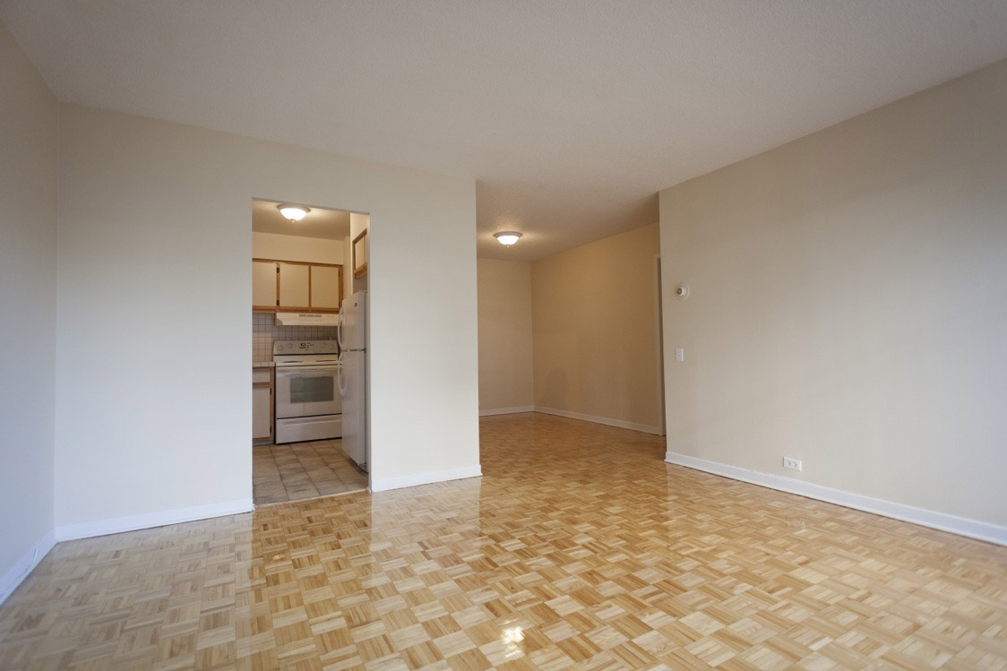 Not Sure for rent at 1 Place De La Belle-Rive, Laval, QC. This is the empty room with stainless steel, tile floor and vaulted ceiling.