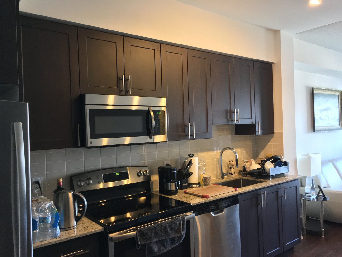 Condo for rent at 7161 Yonge Street, Markham, ON. This is the kitchen with stainless steel and hardwood floor.
