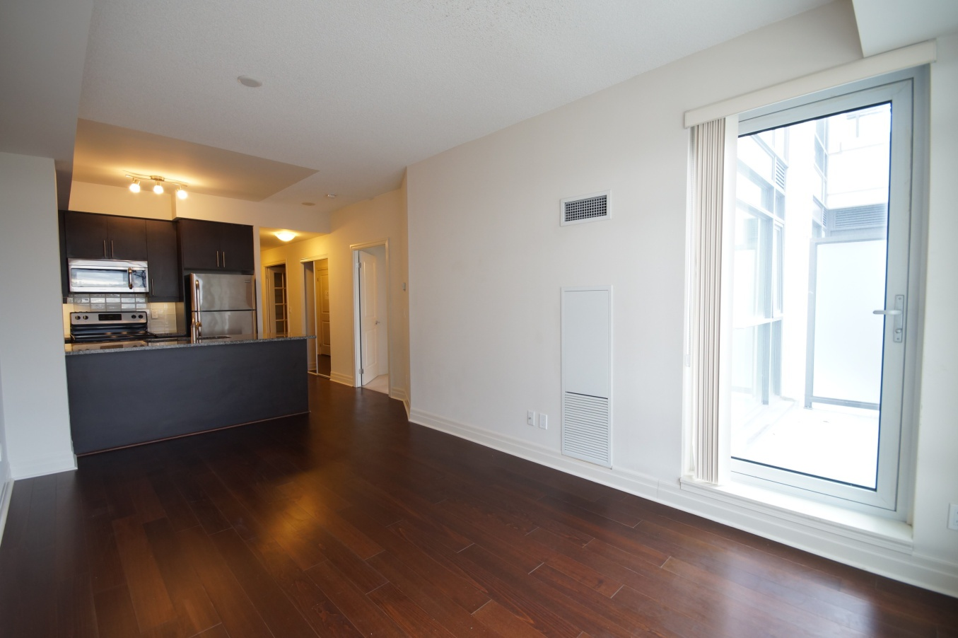 Condo for rent at 8130 Birchmount Rd, Markham, ON. This is the empty room with natural light, stainless steel and hardwood floor.
