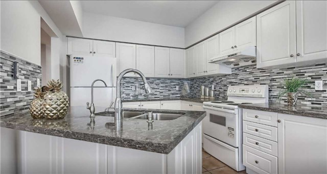 Townhouse for rent at 21 Interlacken Way, Markham, ON. This is the kitchen with tile floor, kitchen island and stainless steel.