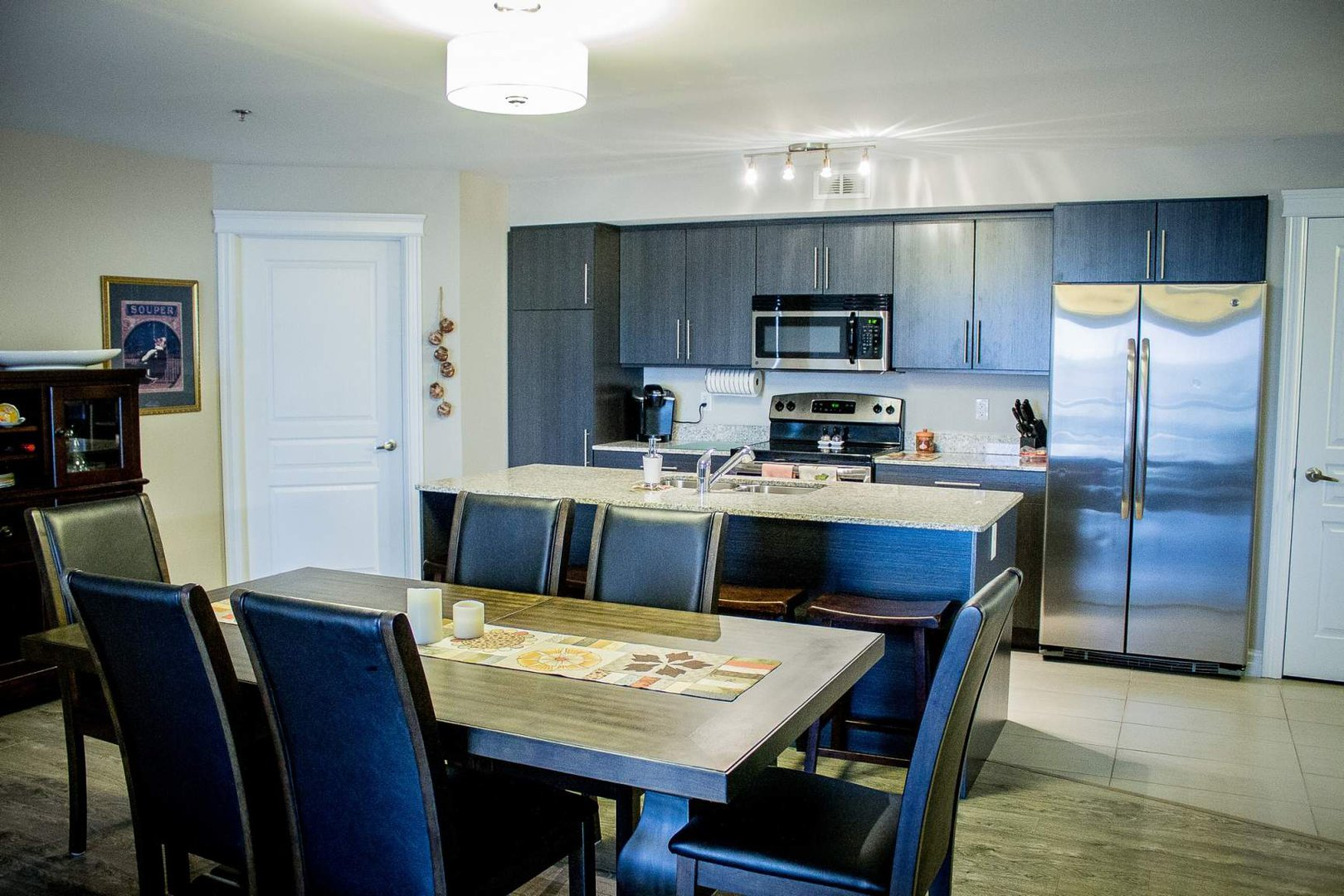 Mid-Rise-Apartment for rent at 747 Coverdale Road, Moncton, NB. This is the kitchen with hardwood floor, stainless steel, tile floor, microwave, refrigerator and oven.
