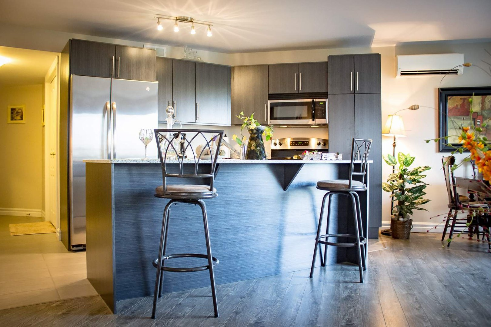 Mid-Rise-Apartment for rent at 747 Coverdale Road, Moncton, NB. This is the kitchen with tile floor, kitchen bar, stainless steel, hardwood floor, wall mounted ac, microwave and refrigerator.