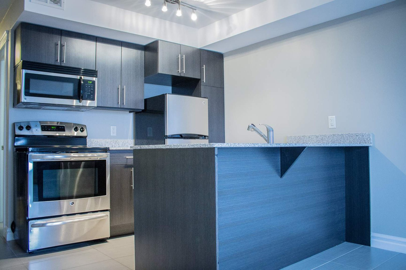Mid-Rise-Apartment for rent at 747 Coverdale Road, Moncton, NB. This is the kitchen with kitchen bar, stainless steel, tile floor, oven and microwave.