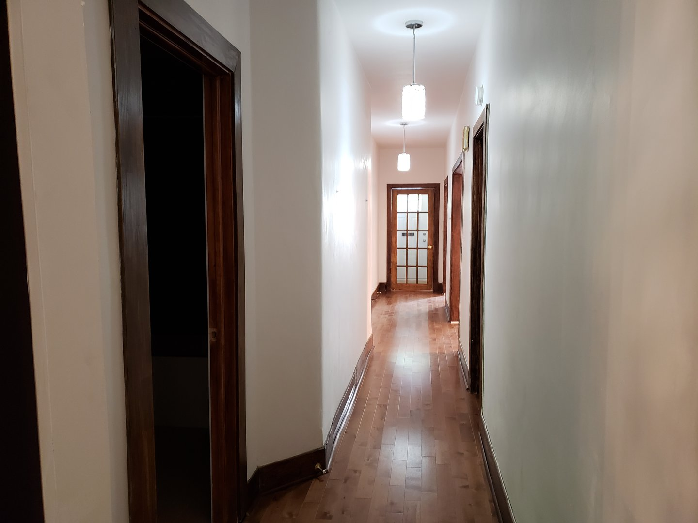 Apartment for rent at 4649 Avenue Clanranald, Montréal, QC. This is the corridor with hardwood floor, french doors and natural light.