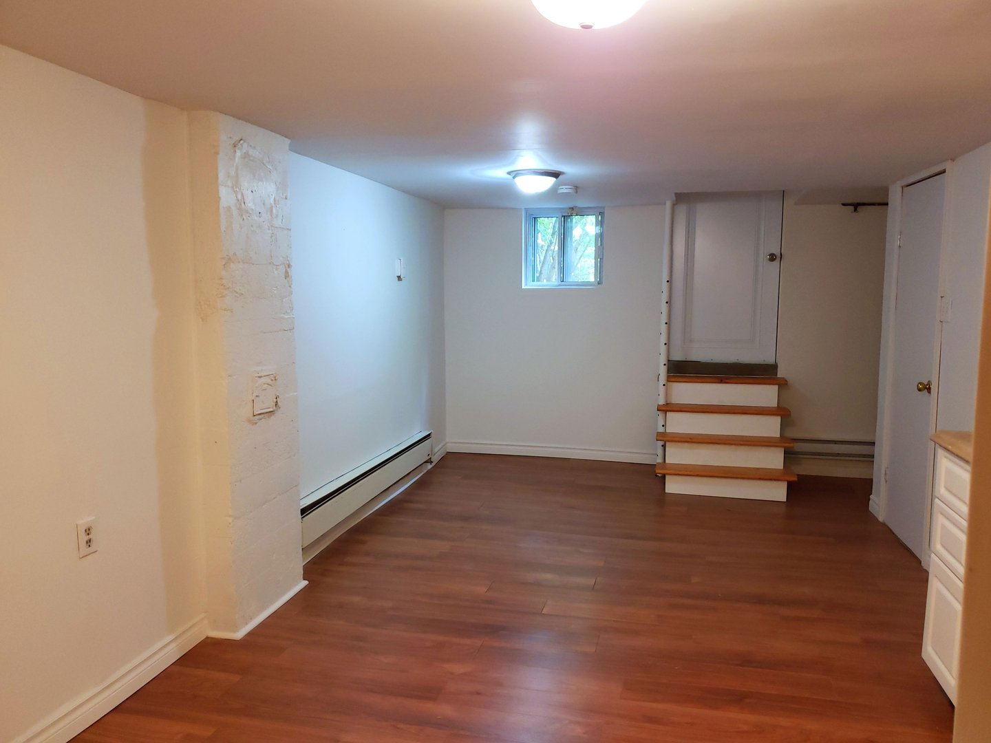 Apartment for rent at 4649 Avenue Clanranald, Montréal, QC. This is the empty room with hardwood floor and natural light.