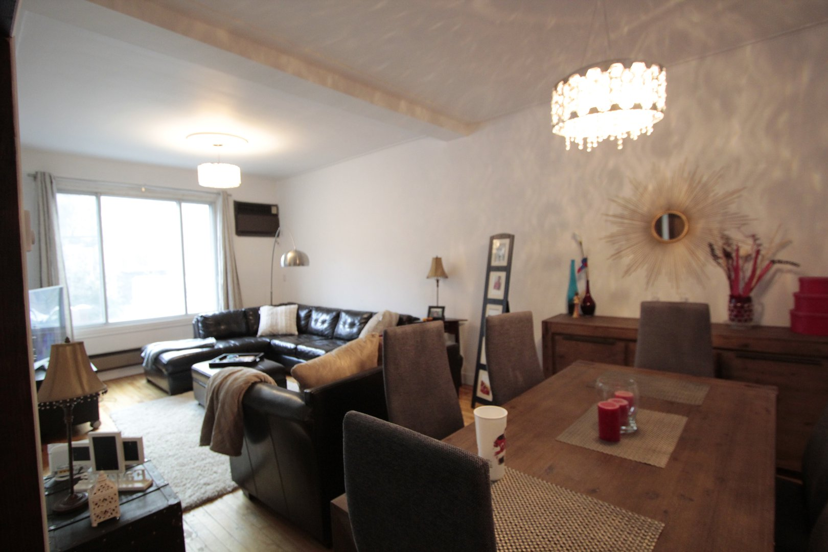 Apartment for rent at 4649 Avenue Clanranald, Montréal, QC. This is the living room with natural light, hardwood floor, beamed ceiling and notable chandelier.