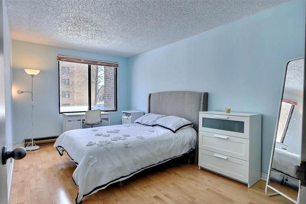 Apartment for rent at 1500 Rue Todd Apt. 102, Montréal, QC. This is the bedroom with hardwood floor and natural light.