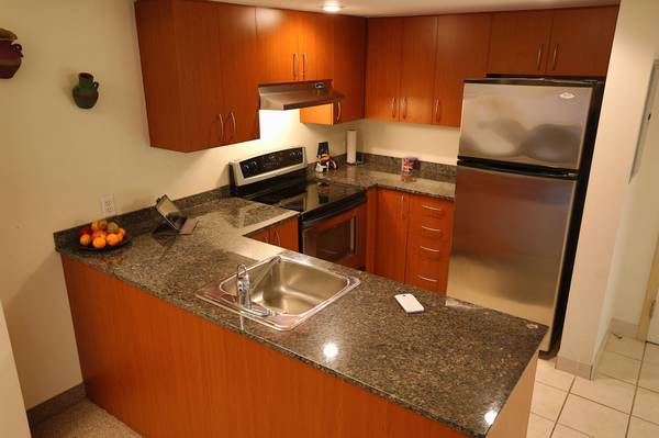 Condo for rent at 88 Rue Charlotte, Montréal, QC. This is the kitchen with tile floor, kitchen island and stainless steel.