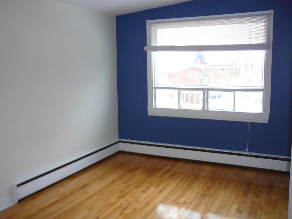 Apartment for rent at 768, avenue de, Québec City, QC. This is the empty room with hardwood floor and natural light.