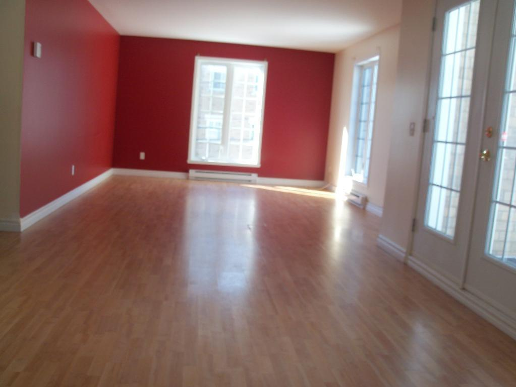 Apartment for rent at 1105-1126 boul., Québec City, QC. This is the empty room with hardwood floor and natural light.