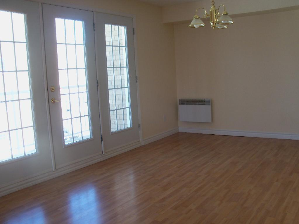 Apartment for rent at 1105-1126 boul., Québec City, QC. This is the empty room with hardwood floor, natural light and notable chandelier.