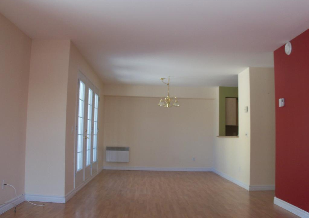 Apartment for rent at 1105-1126 boul., Québec City, QC. This is the empty room with hardwood floor and notable chandelier.