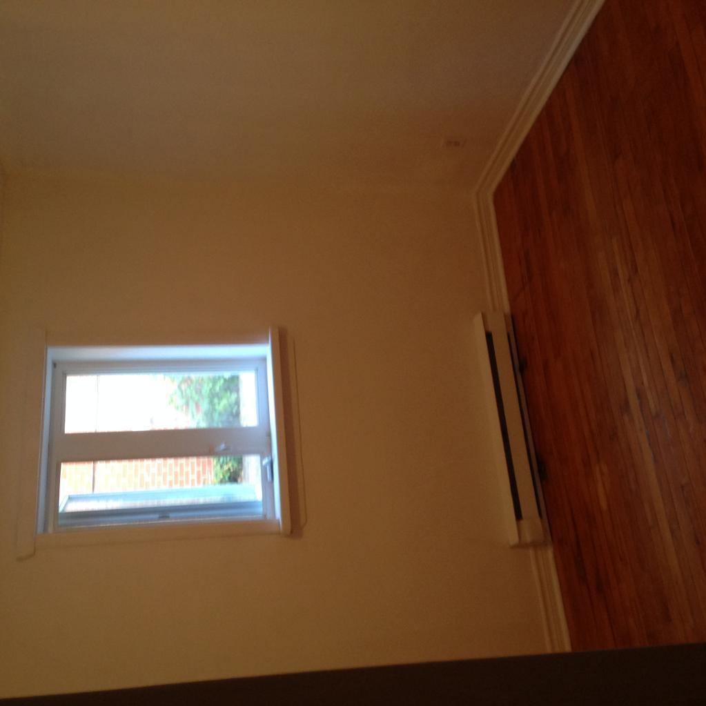 Apartment for rent at 2535 avenue de, Québec City, QC. This is the empty room with high ceiling and natural light.