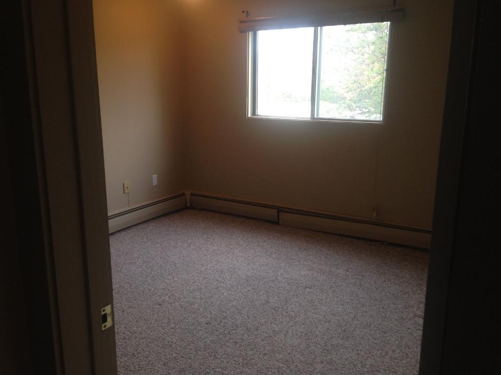 Apartment for rent at 4811-55 Street, Red Deer, AB. This is the empty room with natural light and carpet.