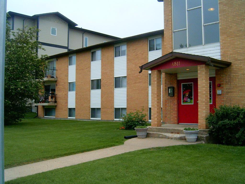 Apartment for rent at 4811-55 Street, Red Deer, AB. This is the front of the house with lawn.