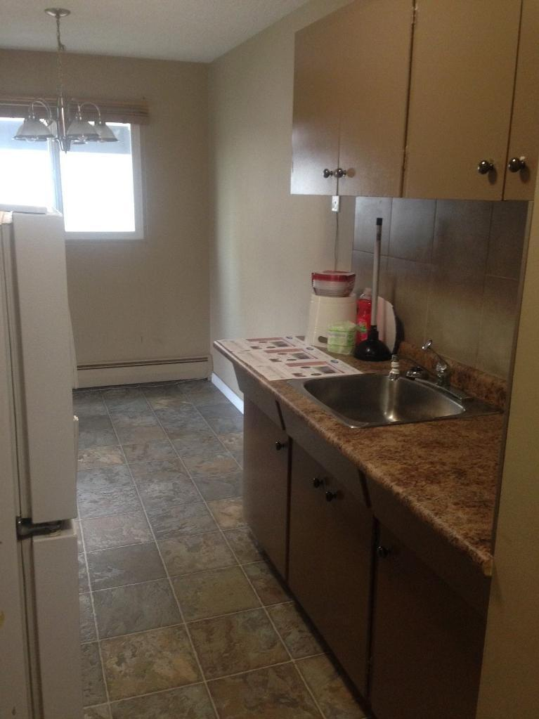 Apartment for rent at 4811-55 Street, Red Deer, AB. This is the kitchen with refrigerator, radiator, tile floor and natural light.